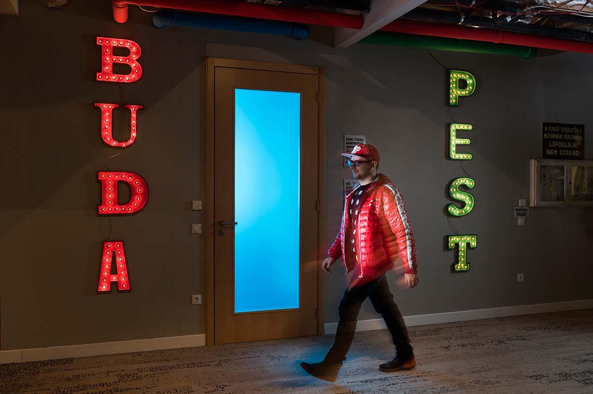 A Google Budapest iroda világító Buda és Pest feliratokkal a falakon. A mennyezeten színes csövek futnak, a két felirat által közrezárt üvegbetétes ajtó előtt pedig épp a Google csapatának egyik tagja sétál el.