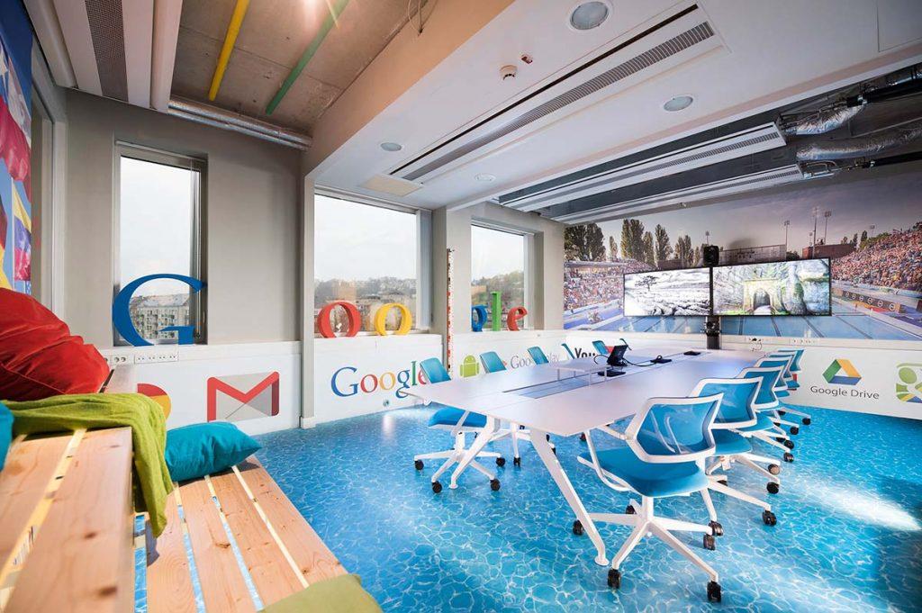 A Google Budapest iroda tárgyalóterme nyomtatott, vizet imitáló padlóval, hatalmas plasztikus Google felirattal az ablakokban, nagyméretű képernyőkkel és egyéb díszletekkel berendezve.
