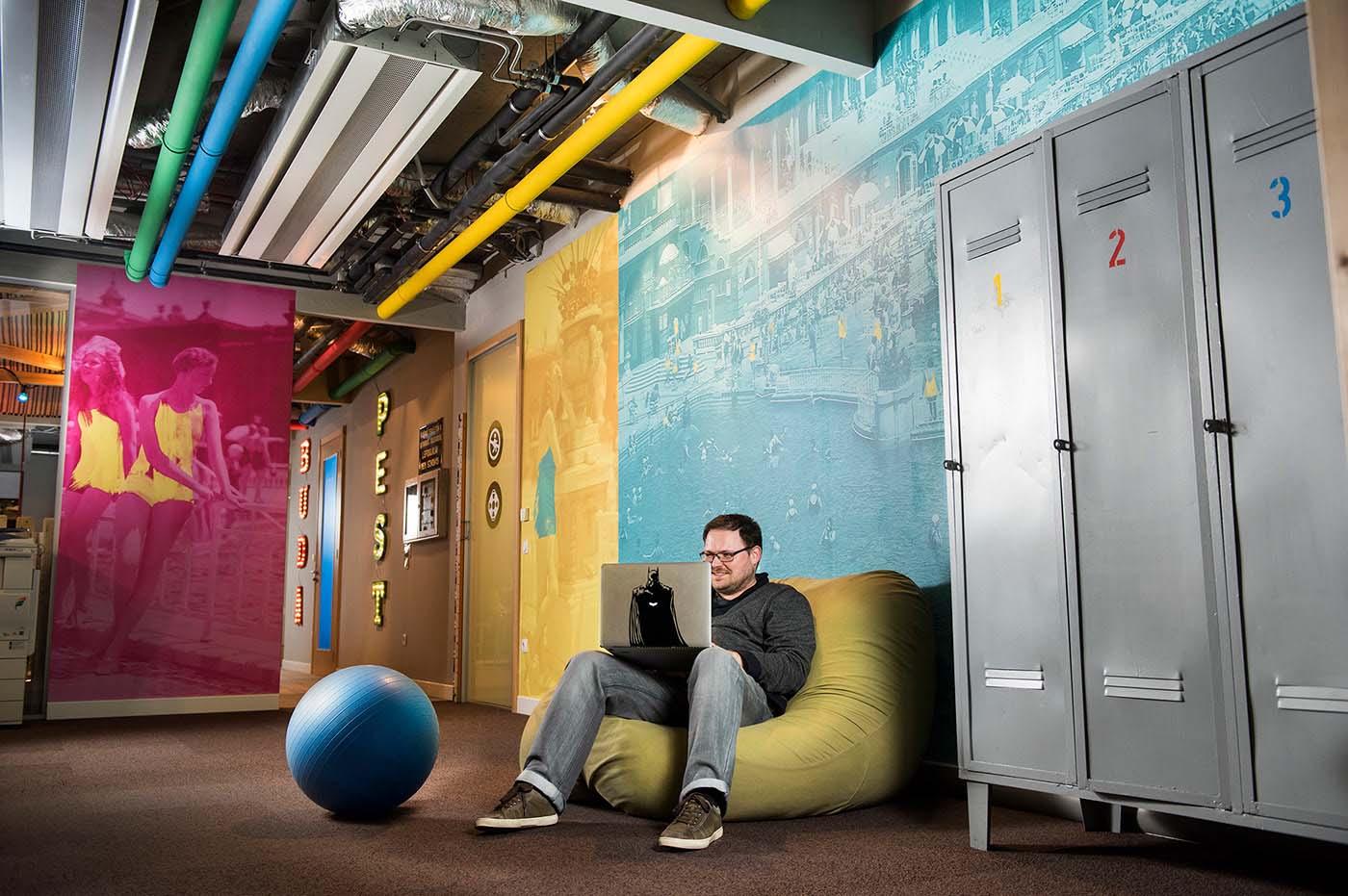 A Google Budapest iroda központi helyisége színes, nyomtatott faldekorációkkal, uszodai szekrényekkel, labdával és babzsákkal, amiben kényelmesen lehet dolgozni.