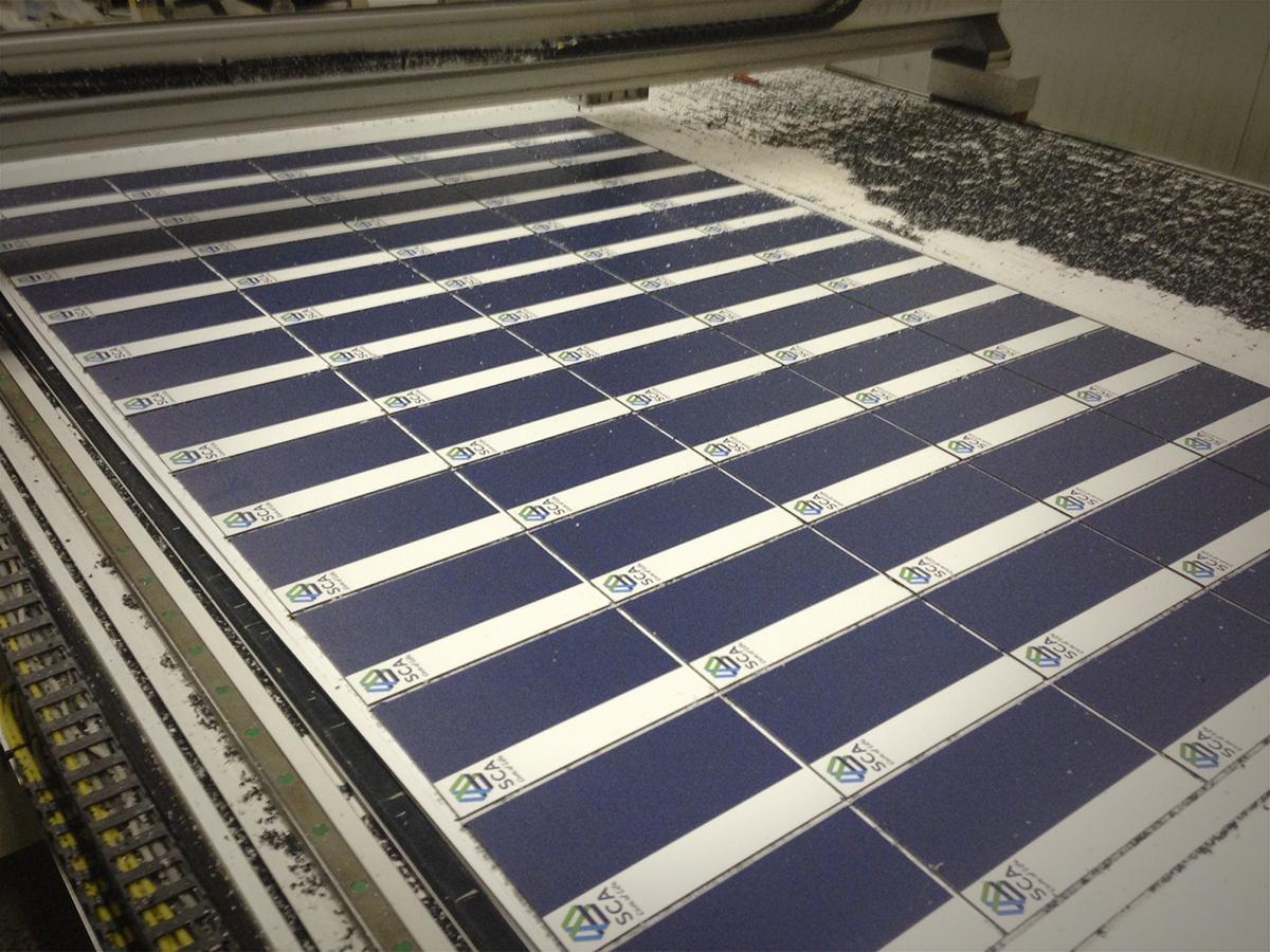 Egy ipari kivágógép precízen felvágja a nagyméretű plexitáblára nyomtatott SCA irodai névtáblákat.