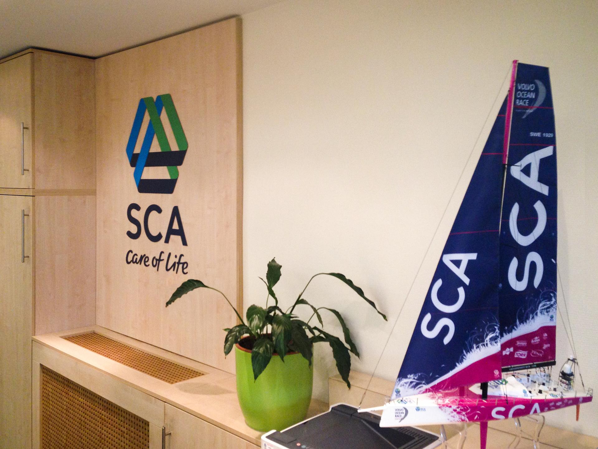 Az SCA irodája nagyméretű SCA logóval, szobanövénnyel és egy SCA arculati színeit viselő sportvitorlás makettjével az előtérben.
