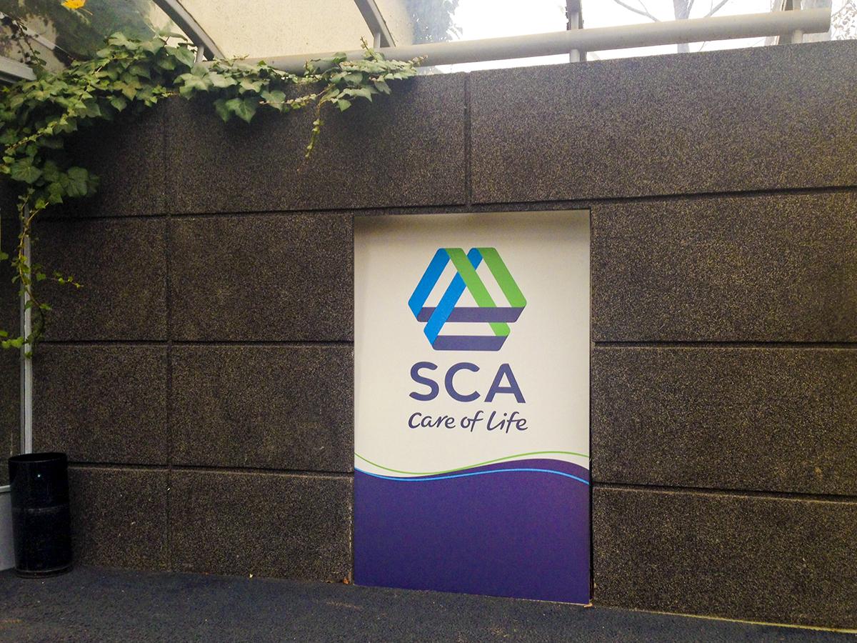 Nagyméretű, az SCA logóját és arculati elemeit viselő plexitábla tölti ki az iroda bejárata mellett falon található szögletes nyílást.