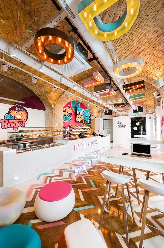 Dizájnos belső tér, amiben a halvány rózsaszín, halványkék és főleg a fehér színek dominálnak. Világító Bagel&Donut felirattal a fényes fehér plexipulton, a háttérben színes faldekorációkkal és elegáns tartókkal a különleges fánkok számára. Az étkezőtérben fehér dizájner asztalok és székek kaptak helyet a csillogó játékos padlón, felettük fehérre festett csövek és spotlámpák láthatóak, amik mellett világító tömbbetűk kaptak helyet.