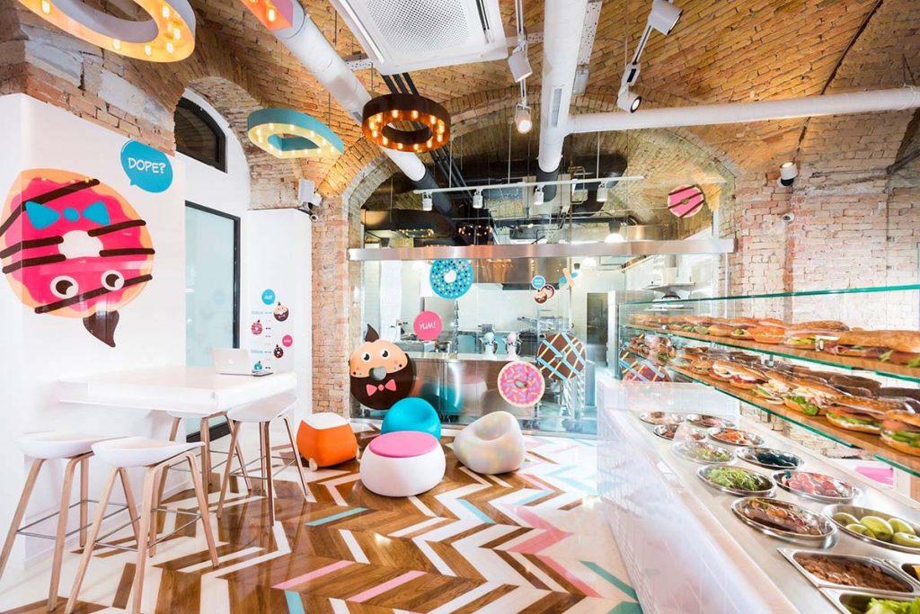 Dizájnos belső tér, amiben a halvány rózsaszín, halványkék és főleg a fehér színek dominálnak. A fehér plexipult végén üvegtárolóban szendvicsek sorakoznak. A pulttal szemben és a konyhát az étkezőtértől elválasztó dekorált üvegfal előtt fehér dizájner asztalok és székek kaptak és színes legömbölyített ülőgarnitúra elemei kaptak helyet. Felettük fehérre festett csövek, spotlámpák és világító tömbbetűk lógnak a rusztikus téglákkal borított boltozatos mennyezetről.