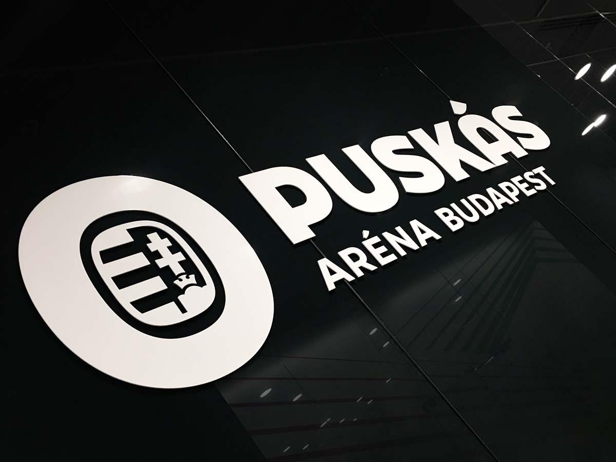 Elegáns, nagyméretű fehér plexi Puskás logó a fényesen csillogó fekete plexifalon.