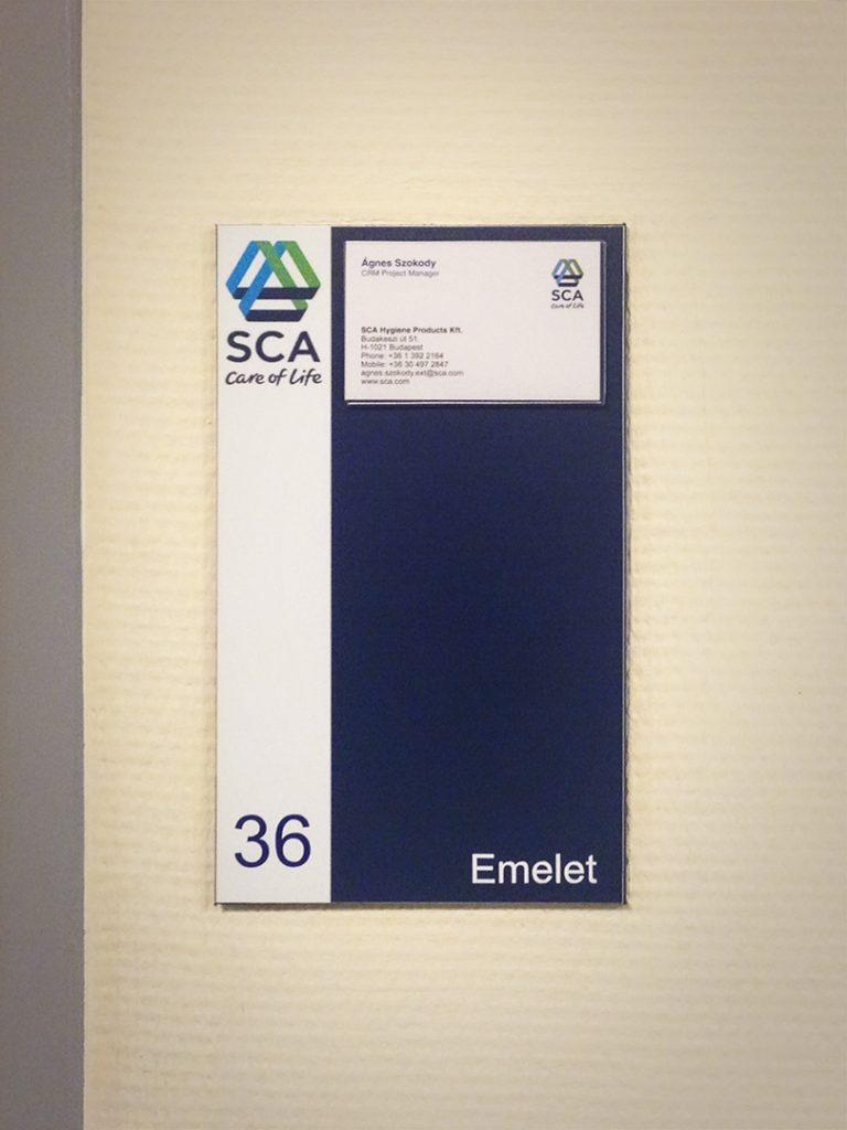 SCA irodai névtábla a falon.