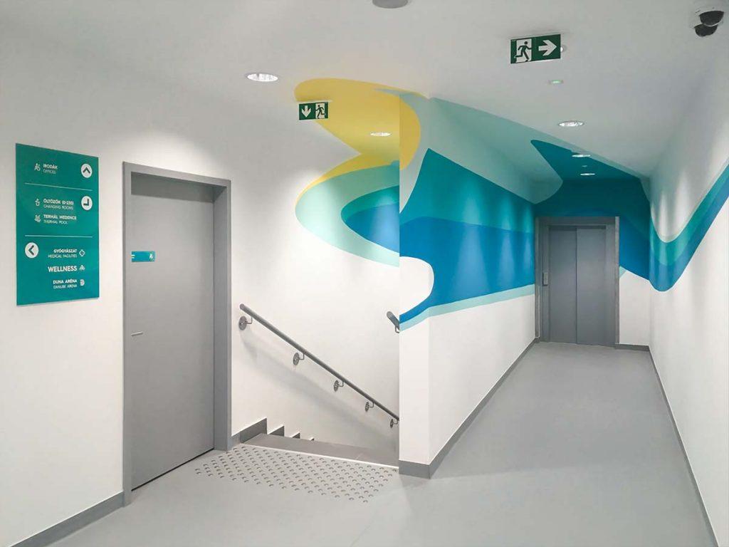 A Duna Aréna belsőtéri dekorációja geometrikus, festett falfelületekkel és elegáns színes irányítótáblákkal.