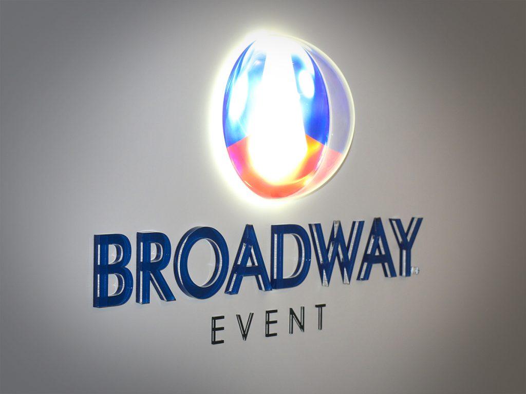 Átlátszó félgömb alakú burában elhelyezett vörös és kék színben világító Broadway logó az iroda fehér falán, alatta kék és fekete plexiből kialakított Bradway Event felirattal.