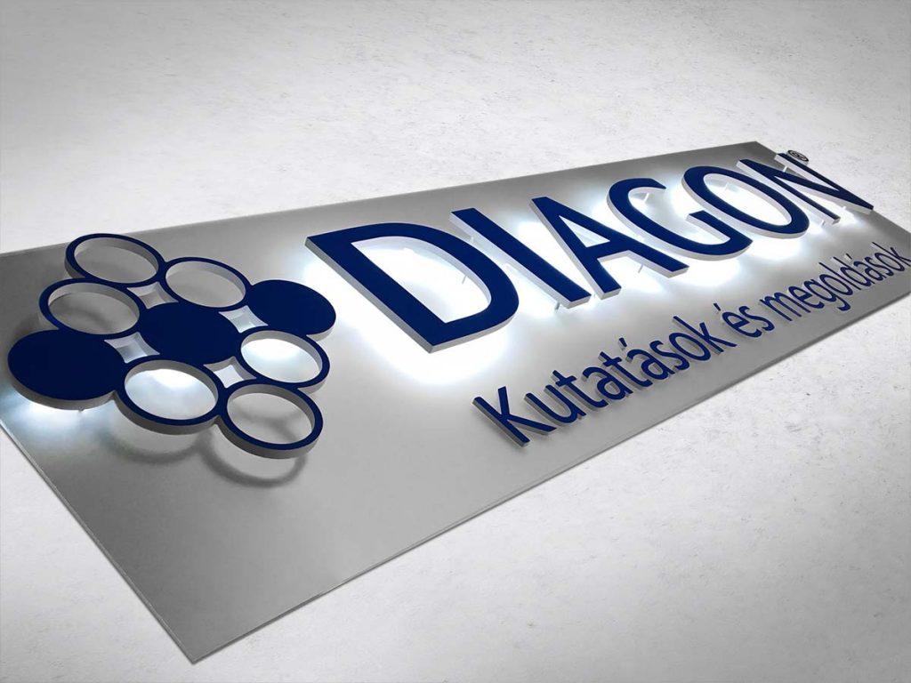 Kék színű Diagon indirekt világító felirat fehér hordozólapon. A betűk hátuljában elhelyezett fényforrások fénye visszaverődik a fehér felületről így ragyogva be indirekt módon a logót és a hozzá tartozó feliratot.