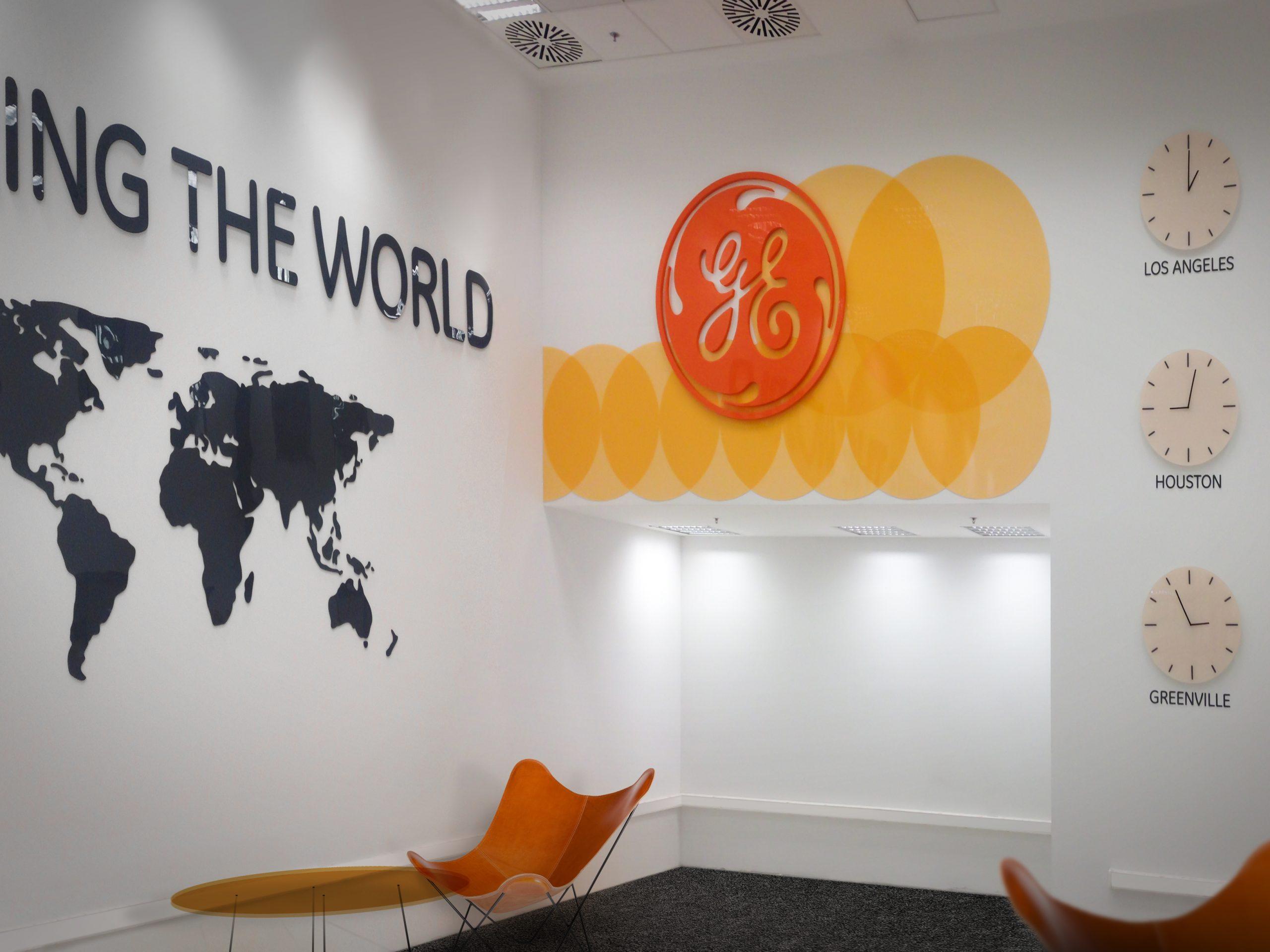 """A General Electric 7-es épületének fogadótere nagyméretű """"Powering the world"""" felirattal és világtérképpel, látványos Narancs színű GE logóval, mögötte egyedi sárga faldekorációval és világórákkal a falon."""