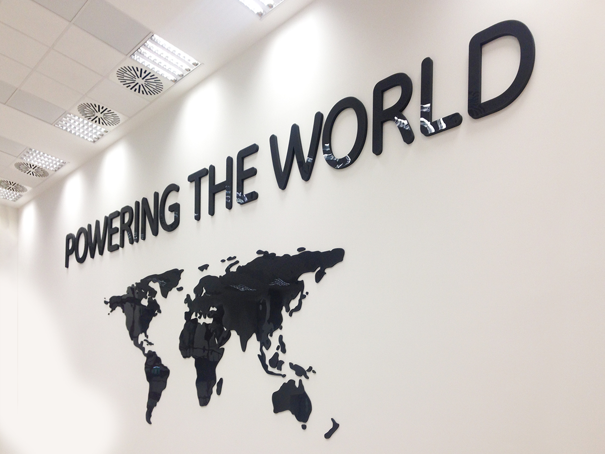 """Hatalmas """"Powering the world"""" felirat és világtérkép fényes fekete plexiből."""