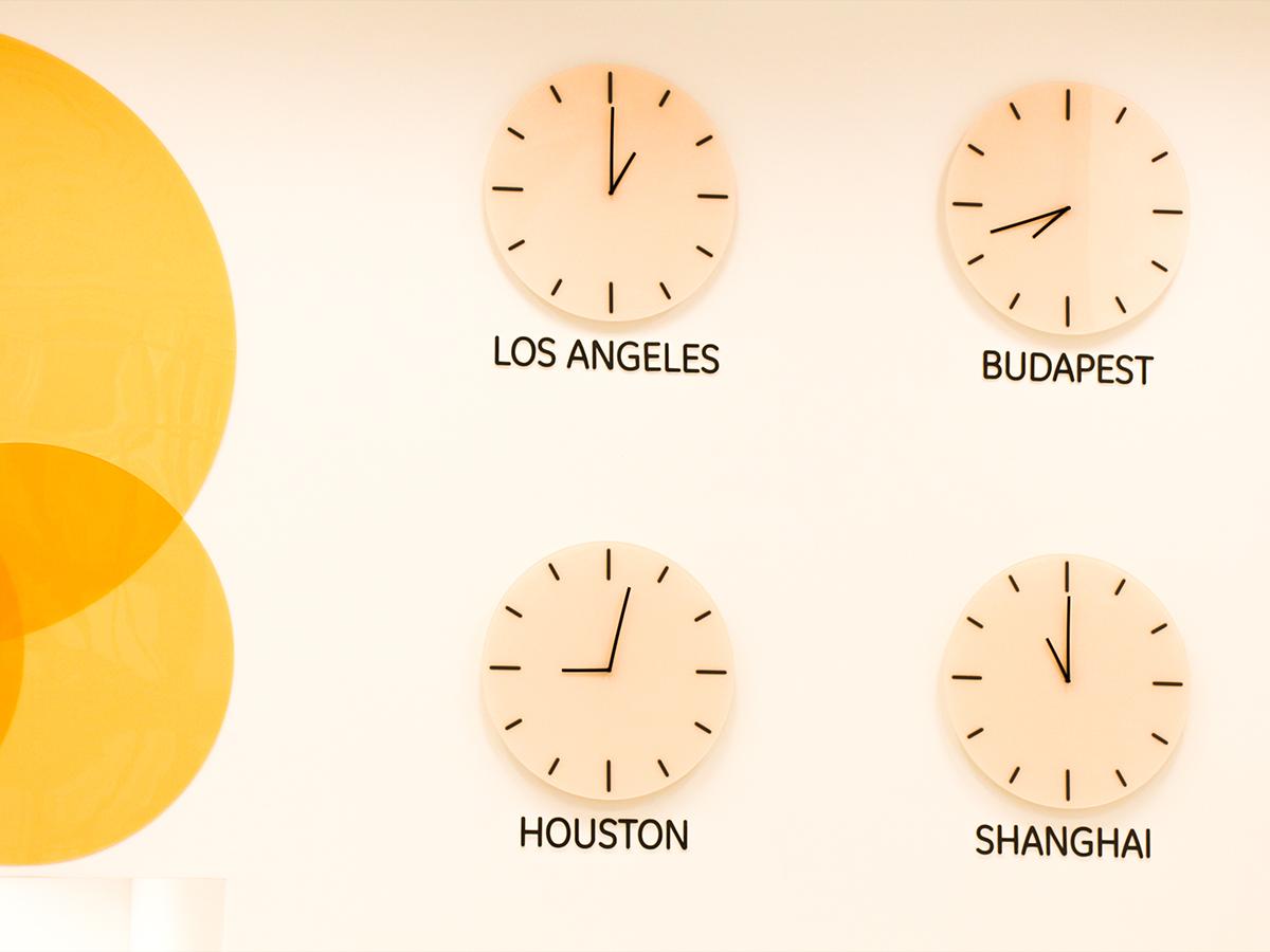 Egyedi világórák (Los Angeles, Budapest, Houston, Shanghai) a falon.