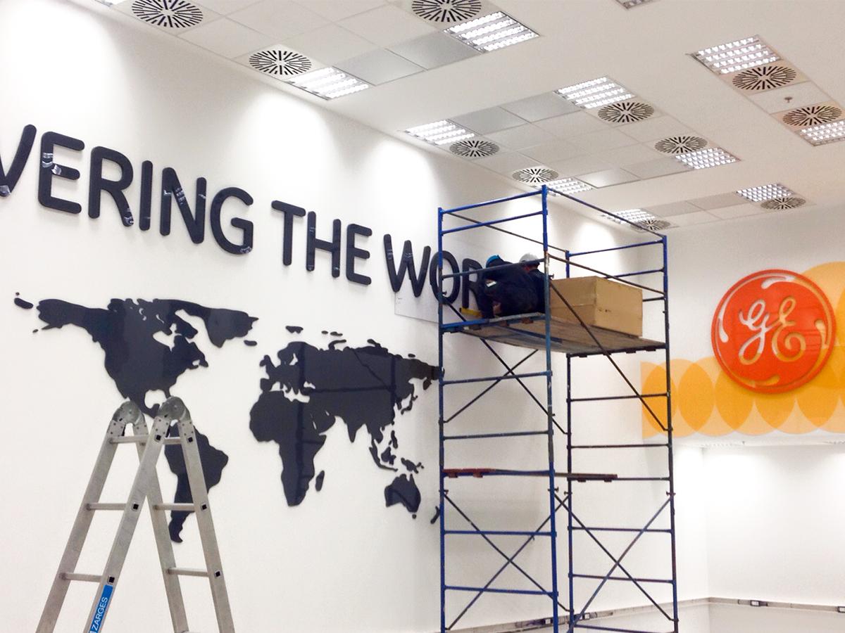 """Két munkás egy magas állvány tetején rögzíti a """"Powering the World"""" felirat utolsó néhány betűjét."""