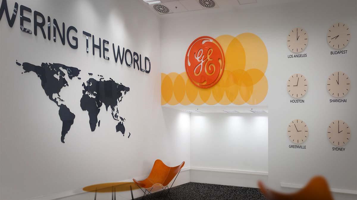 """General Electric 7-es épület váróterme nagyméretű """"Powering the World"""" plasztikus felirattal, világtérképpel, a cég nagyméretű logójával és világórákkal a falon."""