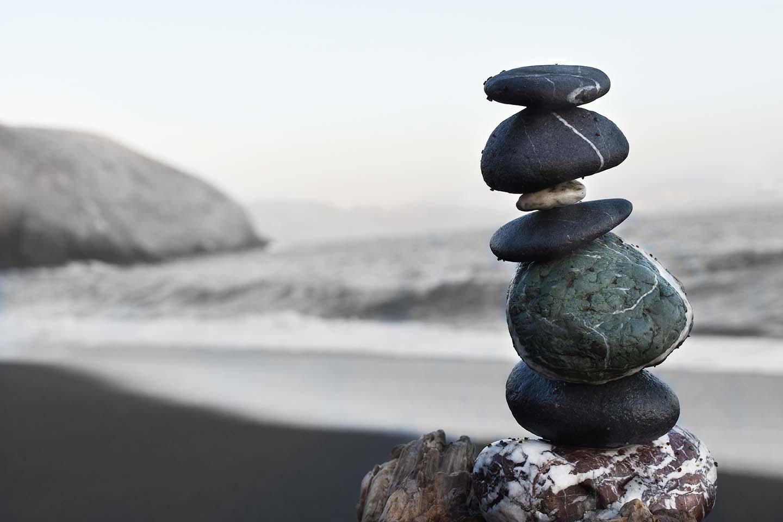 Egymáson egyensúlyozó dekoratív kövek csendes, nyugodt tengerparttal a háttérben.