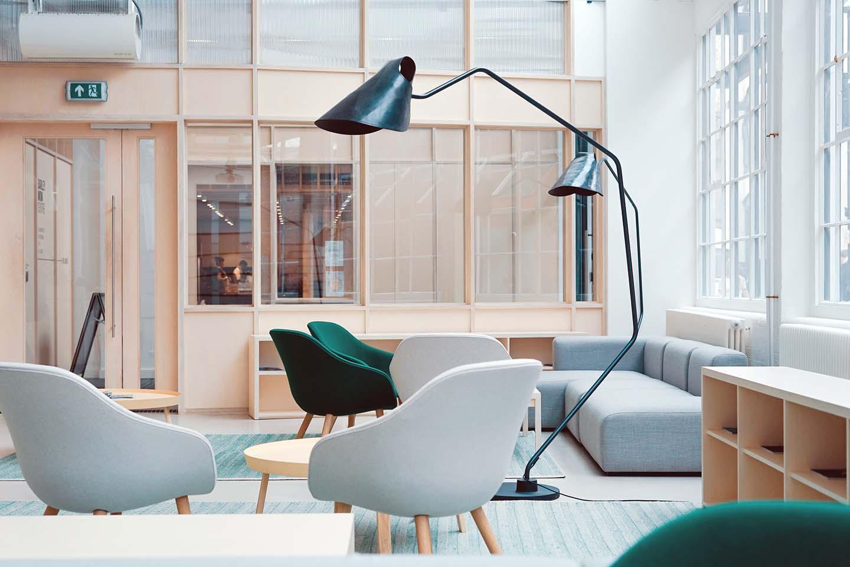 Stílusosan berendezett világos, minimalista iroda fehér és zöld fotelekkel és lámpákkal.