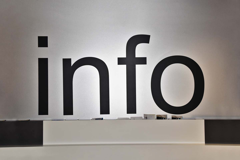 """Hatalmas fekete """"info"""" felirat a fehér falon, alatta felület kialakítva az elvihető információs füzeteknek."""